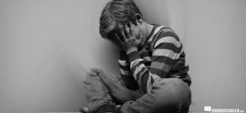 Burnout bei Kindern - Junge sitzt traurig am Boden
